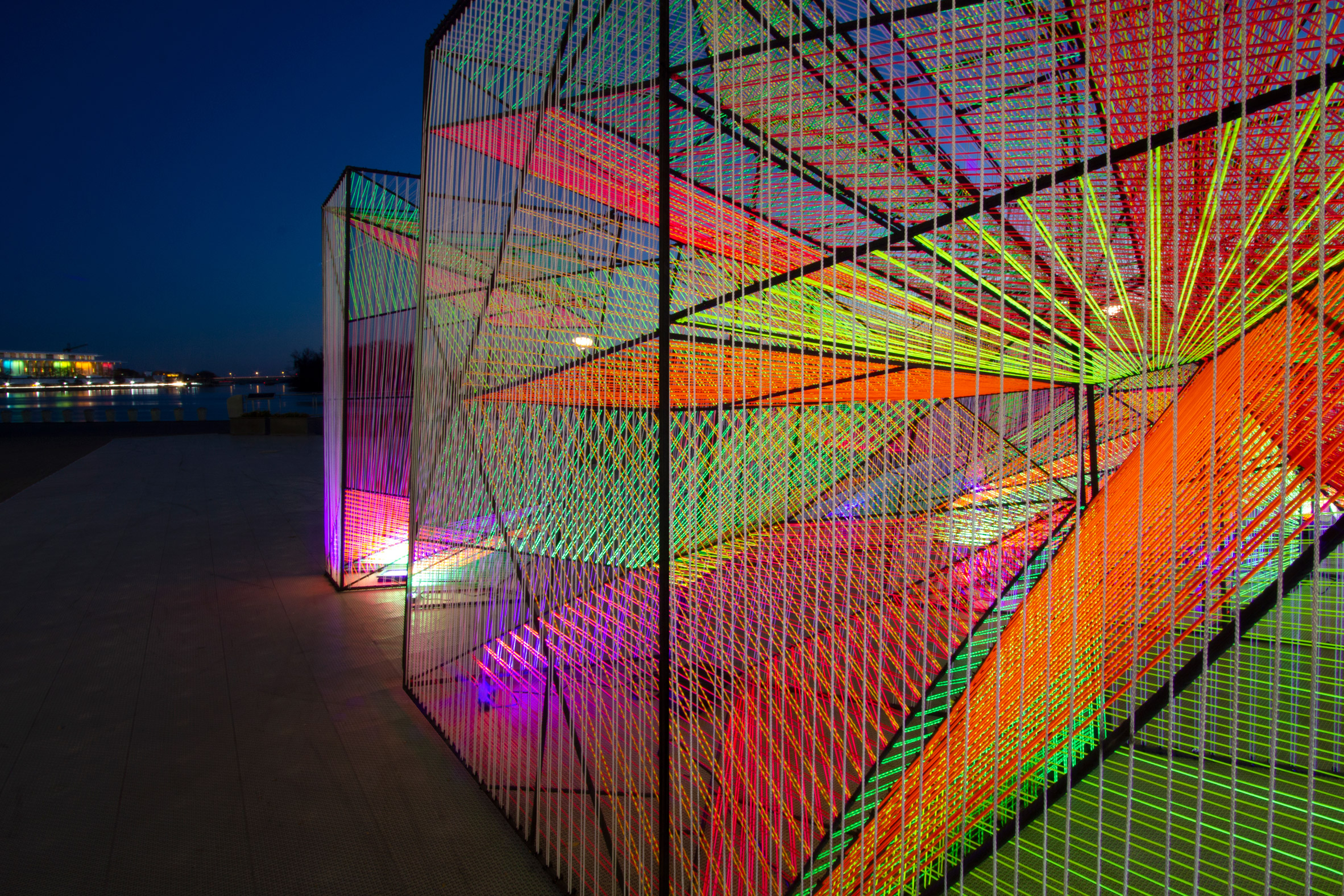 "Prismatic is the engaging sculptural installation by architecture and design studio Hou de Sousa, which is currently at the Senator Charles H Percy Plaza in Washington DC. Described as a ""kaleidoscopic experience of light, color and space"", the project features nine geometric forms in black steel frames, wrapped in fluorescent cords that create wavy and repetitive patterns. Moving through the sculptures gives the effect of a surface in motion. The work is lightweight enough to be transported easily (the installation was assembled in Brooklyn) but sturdy enough to withstand any weather changes it encounter along the way. Photography: Hou de Sousa"